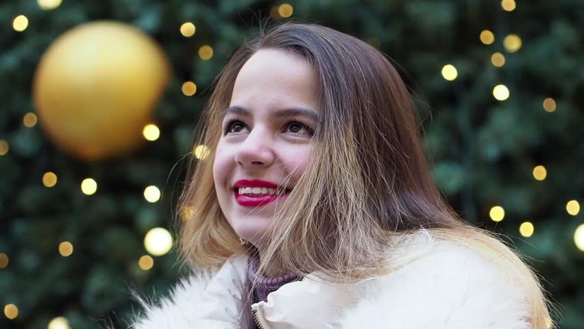 Young, pretty model brunette poses in the winter near a Christmas tree in the middle of a winter city park, dressed in a light fur coat | Shutterstock HD Video #1024729439