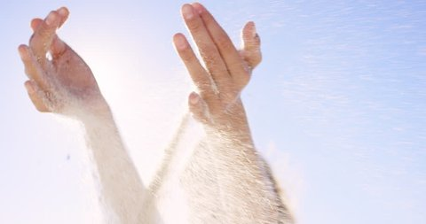 Close up of woman pouring sand running through fingers slow motion at the beach with sun flare and blue skye REG DRAGON