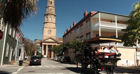 Charleston, South Carolina, USA – October 23, 2018: People take a carriage ride by St. Philip's Church in historic downtown Charleston South Carolina USA.
