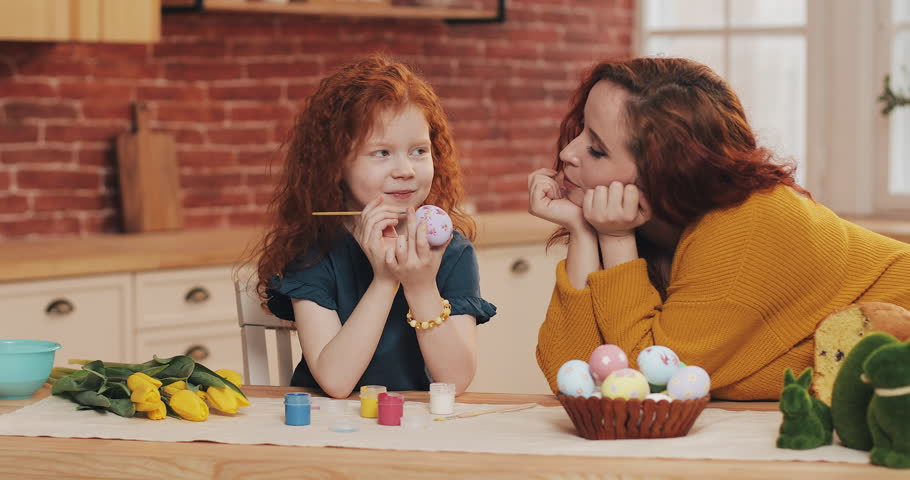 Mom and her little daughter are preparing for Easter. Little girl painting Easter eggs in cozy kitchen. Smiling mother looks at her daughter | Shutterstock HD Video #1024753589
