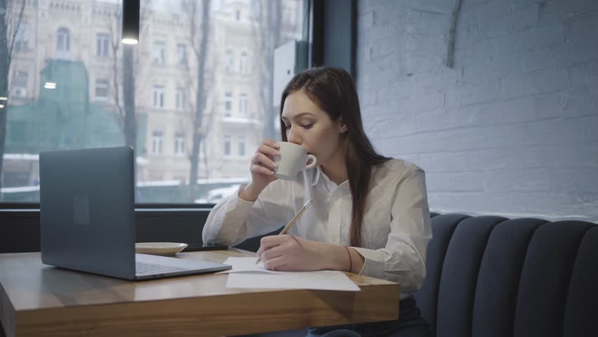 Concentrated woman using her laptop sitting at the table in cafe. Girl sitting on the sofa near window drinking coffee and writes down information checking the laptop screen | Shutterstock HD Video #1024770959