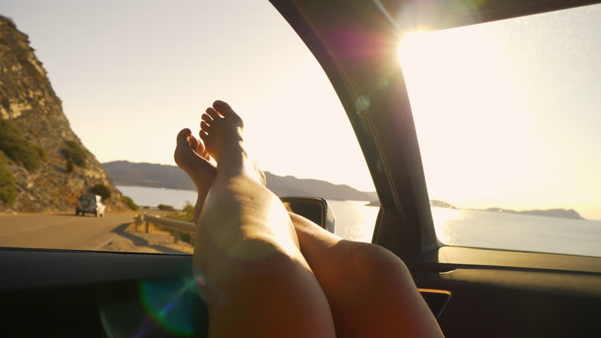SLOW MOTION, SUN FLARE, POV: Sitting in car with your bare feet out the window while watching the picturesque French seaside. Carefree female tourist stops by the side of the road to rest during trip.   Shutterstock HD Video #1024777109