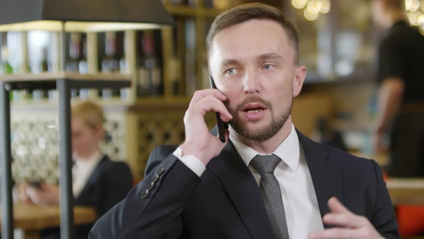 Tilt down of Caucasian man in office wear sitting in café and talking on cellphone | Shutterstock HD Video #1024795589