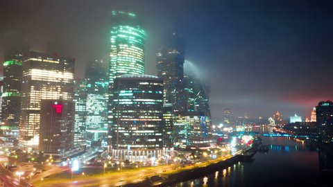 Amazingly beautiful hyperlapse of Moscow City Business Center on the foggy night with glittering lights from buildings, streets and traffic. Close up aerial shot. 8K ultra high definition footage.