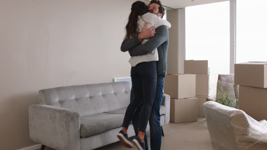 young couple moving house new home owners smiling enjoying successful move hugging in apartment #1024808069