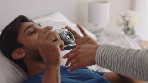 happy couple taking photos together using camera having fun at home on bed playfully enjoying romantic relationship photographing each other