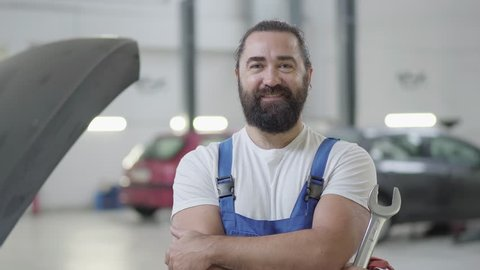 Portrait of a smiling bearded mechanic posing with a wrench standing at an auto repair shop on the background of a broken car.