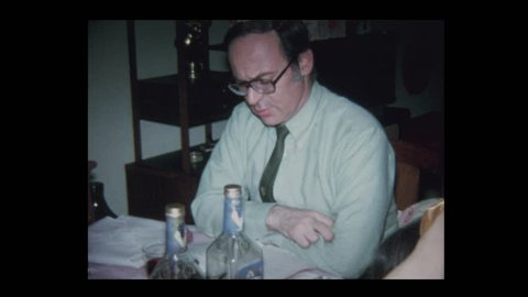 N. Belmore, New York, USA- 1971: Man reads from Haggadah to family at Passover seder