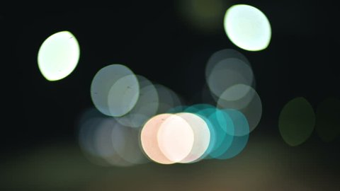 Colored bokeh lights in the night country road. moving circles of traffic highway lights. Defocused night road