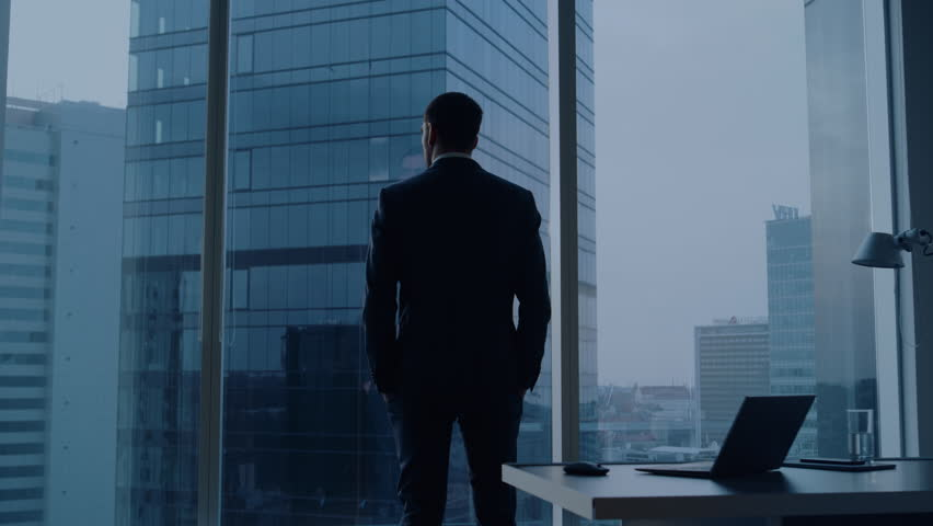Back View of the Thoughtful Businessman wearing a Suit Standing in His Office, Contemplating Next Big Business Deal, Looking out of the Window. Business District Panoramic Window View