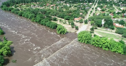 Aerial drone scene of brown strong river passing over bridge. Flood in Mina clavero. Growing river over city streets. Flying backwards discovering flooded town. Cordoba, Argentina