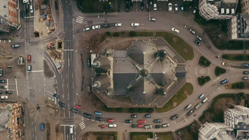 Birdseye view of the Ringkirche in Wiesbaden. Aerial shot filmed by drone with the camera looking down. Light traffic can be seen and the architecture defines circles and squares. | Shutterstock HD Video #1024923689