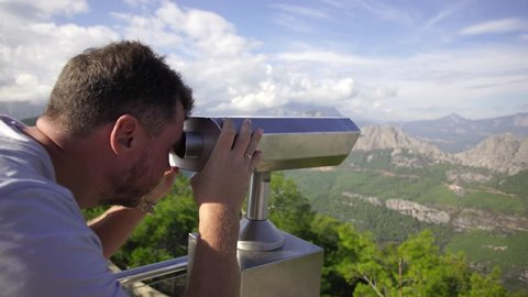 Closeup view of coin operated binocular viewer for looking in details at beautiful summer sea landscape. Antalya, Turkey. Happy adult man looking through it. Summer holidays and sightseeing concept.