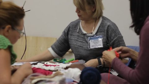 Odessa,Ukraine - December 22 2018:  Woman teacher  conducts the women a masterclass on crochet lace or clothing. Taken from a moving camera on a slider. Camera dolly