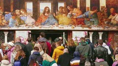 """Minsk, Belarus - Apr 9, 2017: Crowd of parishioners go up the stairs of the Catholic church under the reproduction of Leonardo da Vinci's """"Last Supper"""" on Palm Sunday."""