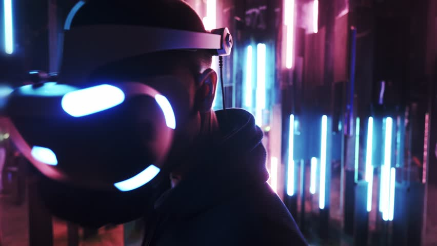 Back view man wearing VR headset quick slopes from side to side while playing in dark space illuminated neon light | Shutterstock HD Video #1025065379