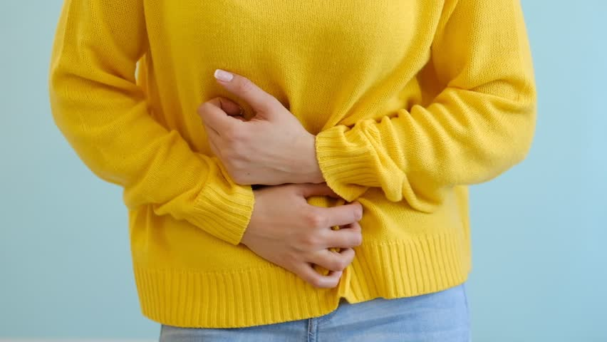 Young woman experiencing stomach pain. people, healthcare and problem concept - woman suffering from stomach ache. suffering from severe pain and cramp in lower abdomen, menstruation. slow motion | Shutterstock HD Video #1025076419