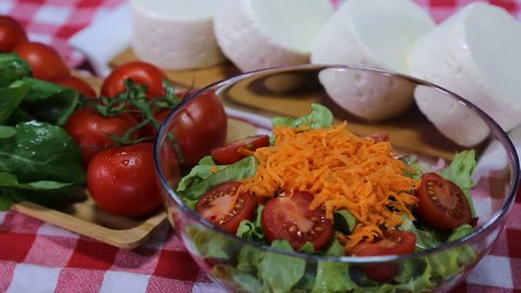Big bowl of salad with carrots and cheese, season salad on red white scotch tablecloth, dropping cheese on salad, vegeterian food, feta cheese