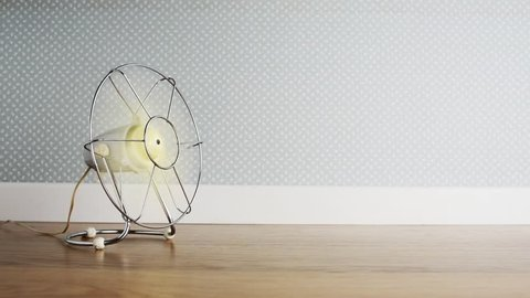 Vintage fan on the floor refreshing air, retro wallpaper on background
