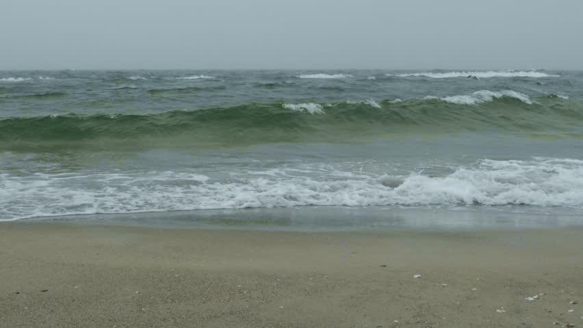 Rough sea with snow storm. Winter sea storm wave strikes the sandy coast. Coastal seascape | Shutterstock HD Video #1025131409