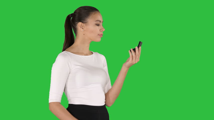 Beautiful woman, dyes her lips lipstick pink, looking in the mirror on a Green Screen, Chroma Key. | Shutterstock HD Video #1025140169