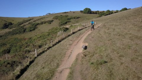 A Mountain biker riding quickly downhill on a cliff path with a view of the sea on a sunny morning