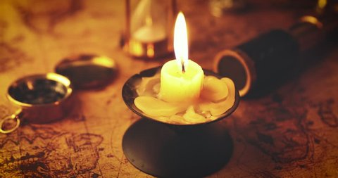 candle in candlestick on the old world map with other retro items (there is no intellectual property infringes, world map is free to use)