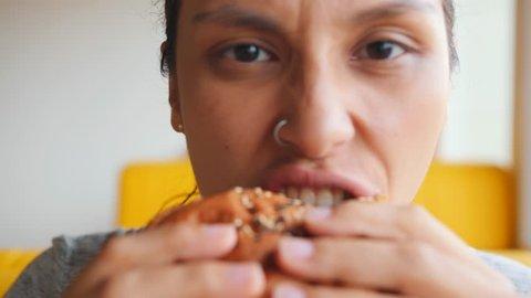 Hungry Girl Eating Vegan Burger in Fast Food Restaurant. 4K Slowmotion.