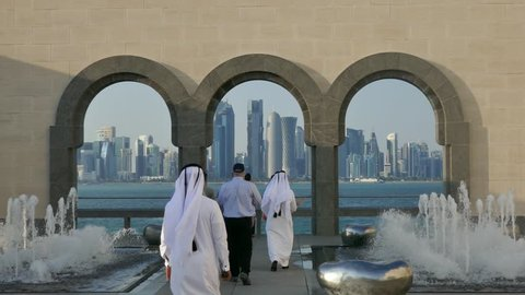 Doha, Qatar, Feb 2019: Group of Arabs and westerners walking towards a viewpoint to the business center of Doha with skyscrapers