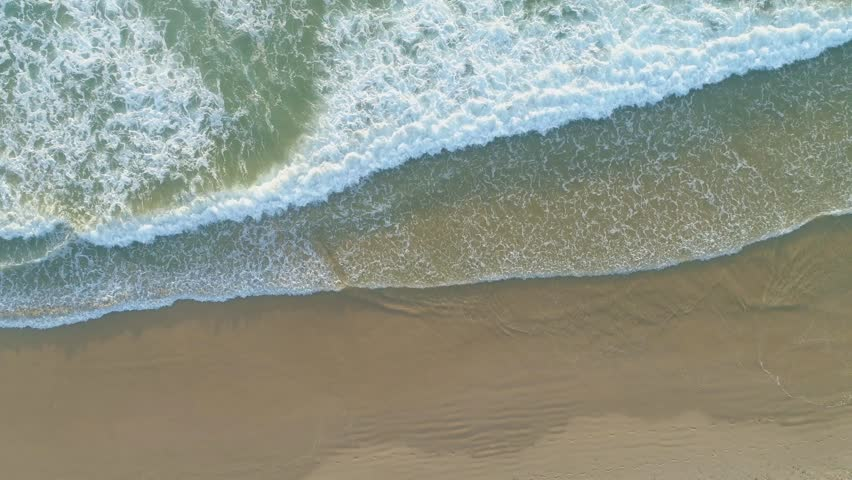 Ocean waves coming onto sandy beach - top down static aerial view | Shutterstock HD Video #1025202359