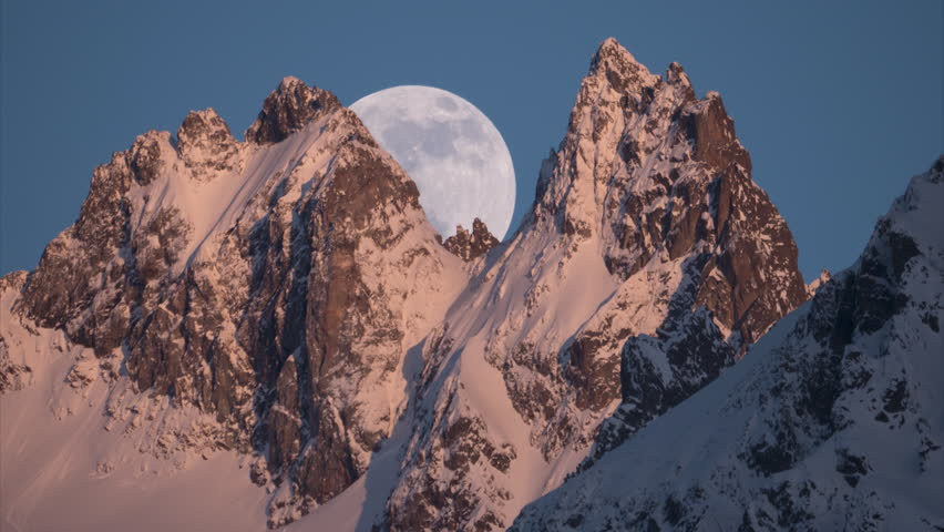 close up full moon rising behind steep mountain peaks as the sun sets time lapse