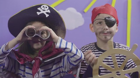 Portraits of two cute children in costumes playing and enjoying in pirate game with props, little girl captain holding spyglass and boy rudder of ship, close up, concept acting and performance, 4k.