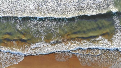 Aerial view of the beach of spain The waves come to the shore and form foam and bubbles off the coast. The look of a dron. Background or Texture