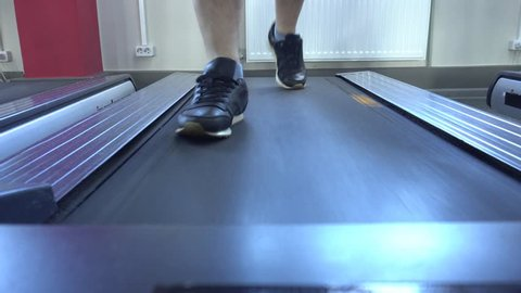 Men's legs run on the treadmill in the gym, lose weight, cardio, close-up, person