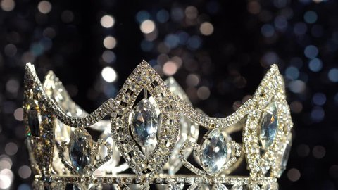 Diamond Silver Crown for Miss Pageant Beauty Contest, Crystal Tiara jewelry decorated gems stone and Bokeh sparking abstract dark background, rotate spin center move around Jewel Crown as Winner Prize