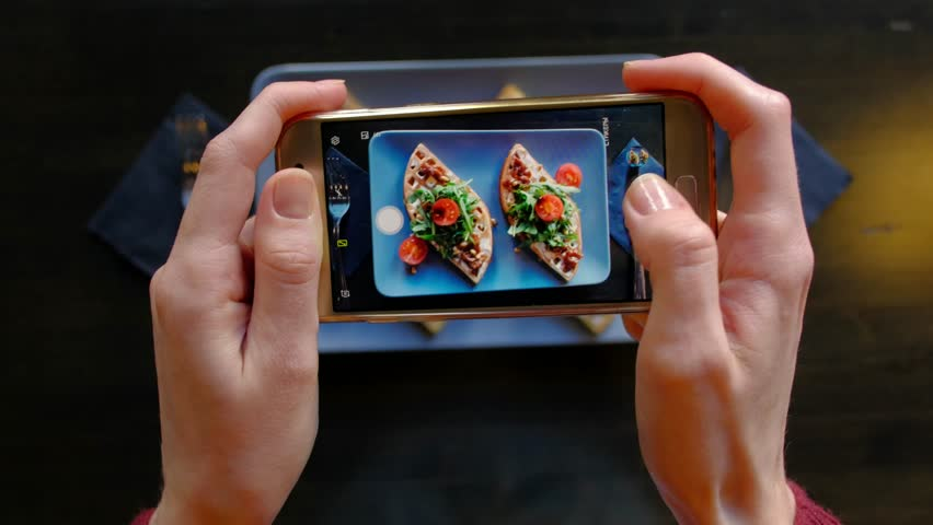 Female hands photographing appetizing food by smartphone in the restaurant. 4k. Delicious fresh waffles with spinach and cherry tomatoes ready in cafe. | Shutterstock HD Video #1025316179