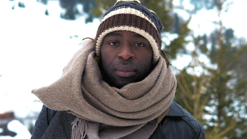 Slow motion. Beautiful trendy black african american man portrait face. Male smiling wearing a hat and a scarf. Static winter mountains close up shot filmed in 4k UHD 2160p | Shutterstock HD Video #1025339699