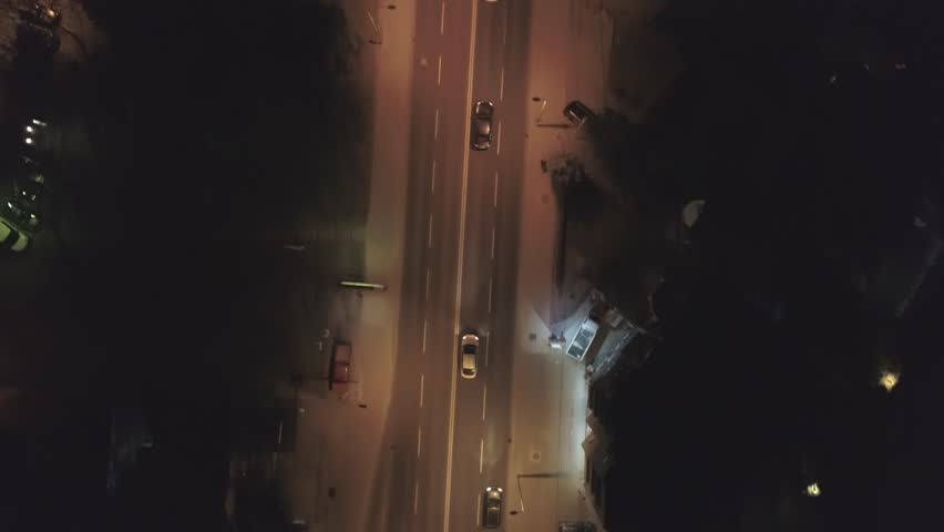 Aerial footage following a car in urban area at night