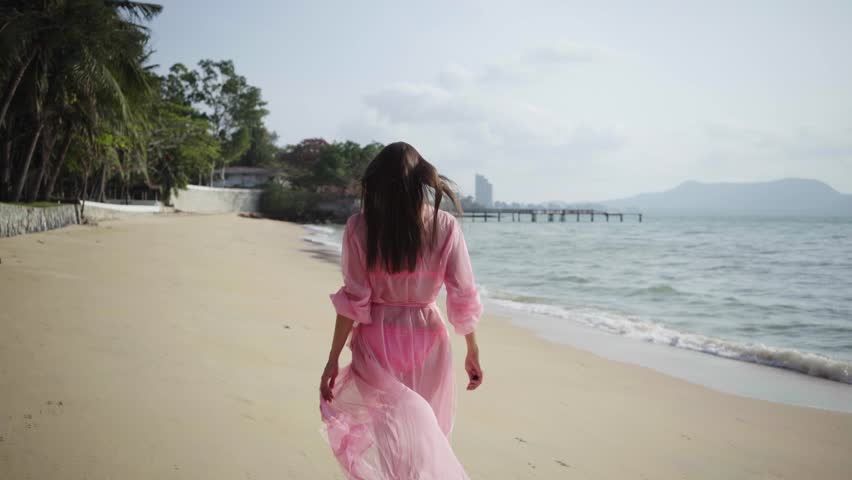 Beautiful female in a long developing pink dress walks walking around spinning on the beach on the rocks. close-up. 4k | Shutterstock HD Video #1025363429
