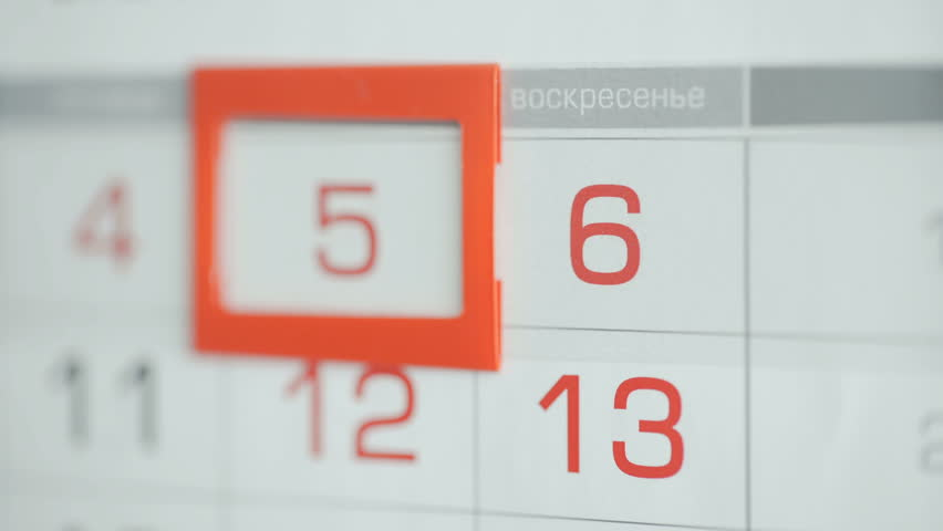 Woman's hand in office changes date at wall calendar. Changes 5 to 6