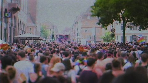 STRASBOURG, FRANCE - CIRCA 2018: VHS tape effect over large crowd of people following gay pride truck at annual FestiGays pride gays and lesbians parade marching French streets fun party atmosphere