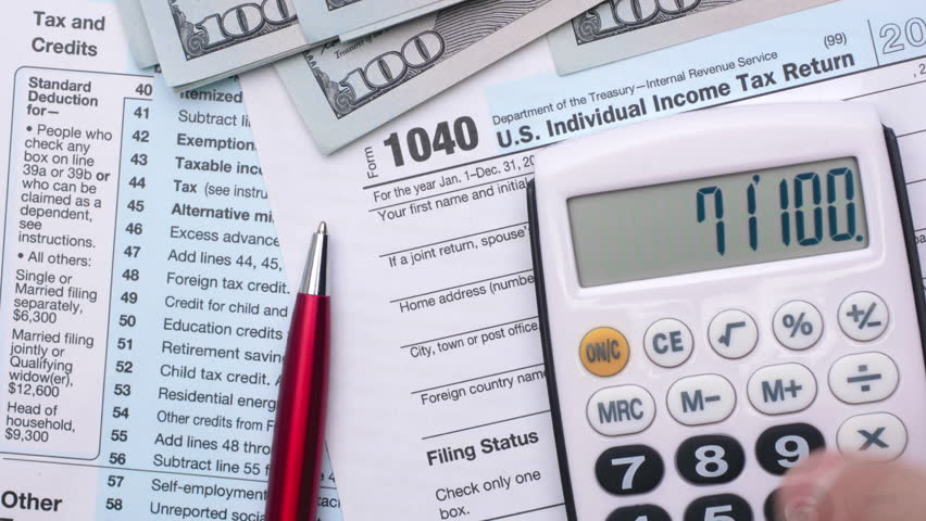 Tax form 1040, pen, dollar bills, and calculator. High angle view.