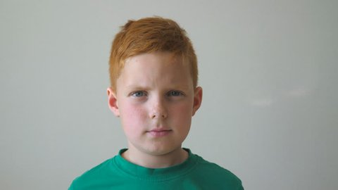 Portrait of young serious red-haired boy with freckles inside. Adorable handsome kid looking into camera indoor. Close up emotions of little male child with sad expression on face. Slow motion