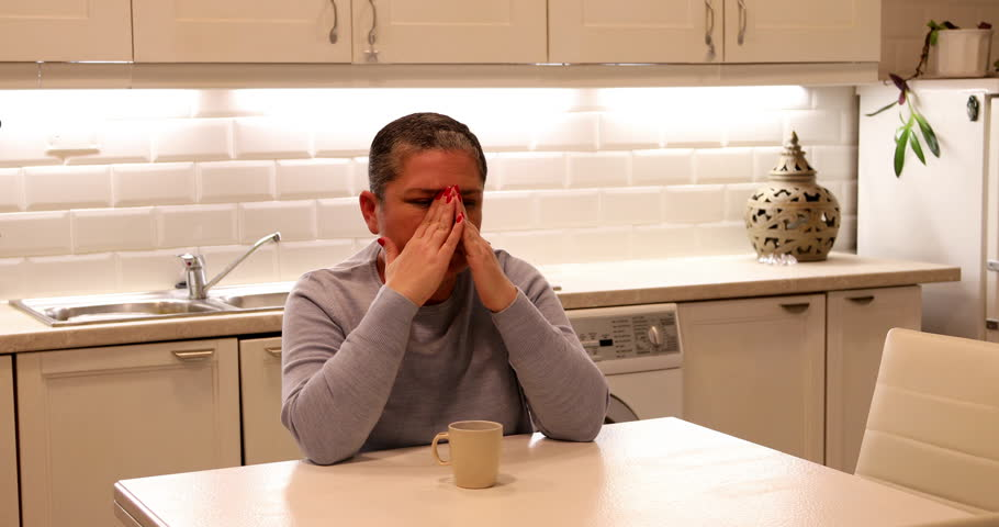 Portrait of a middle aged woman with short gray hair suffering a migraine at home alone | Shutterstock HD Video #1025504699