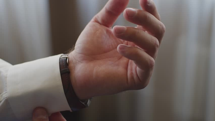 Close-up of a successful man is putting on a wristwatch. Men's hand with a watch, watch on a man's hand, putting the clock on the hand | Shutterstock HD Video #1025538779