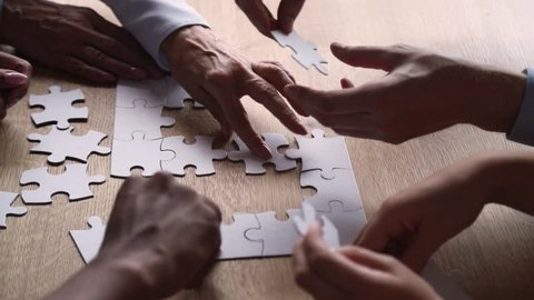 Diverse hands of business people connect puzzle pieces together on office desk, multi ethnic team engaged in finding solution, decision making collaborate in teamwork strategy concept, close up view