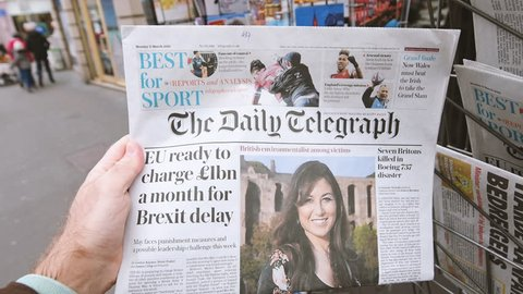 Paris, France - Mar 12, 2019: Man buying press kiosk British newspaper The Daily Telegraph featuring on the cover text that Eu ready to charge 1 billion a month for Brexit delay
