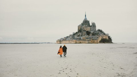 Beautiful cinematic shot, drone follows young happy couple walking towards Mont Saint Michel fortress in Normandy France