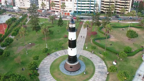 """Aerial view of Faro la Marina located in Miraflores's park by the ocean in Lima, Peru. People, tourists and cyclists having fun in """"Malecon Costa Verde"""". Peruvian lifestyle."""