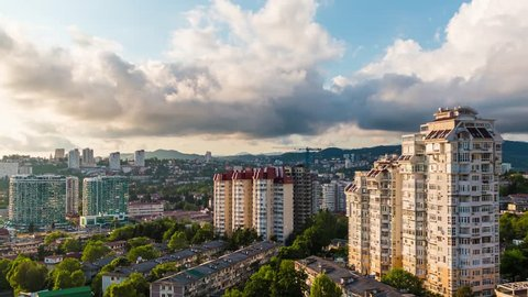 Time-lapse video of day to night transition with panoramic movement from right to left. Aerial view of the apartment district of the city of Sochi, Russia